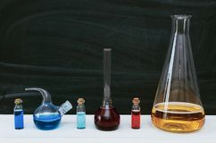 Colorful liquid in chemical flasks and vials. Chemistry. Biology. Colorful fluid in flasks and vials on school blackboard background with copy space. Education stock photography