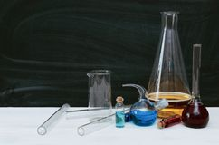 Colorful liquid in chemical flasks and vials. Chemistry. Biology. Colorful fluid in flasks and vials on school blackboard background with copy space. Education royalty free stock photos