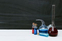 Colorful liquid in chemical flasks and vials. Chemistry. Biology. Colorful liquid in chemical flasks and vials on school blackboard background with copy space royalty free stock photo