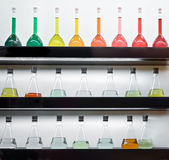 Colorful liquid in flasks laying on shelf. Colorful liquid in flasks laying on wall shelf stock photography