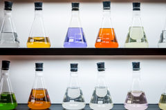 Colorful liquid in flasks laying on shelf. Colorful liquid in flasks laying on wall shelf royalty free stock images