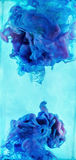 Colorful liquids underwater.  Blue and violet colors mix. Stock Images