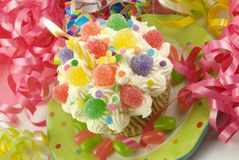 Colorful Lit Birthday Cupcake. A colorful lit birthday cupcake with party decorations, horizontal with copy space, selective focus Royalty Free Stock Images