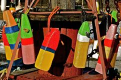 Colorful Lobster Buoys. Old wooden lobster buoys hang from an a rustic wooden spool Stock Photography