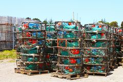 Colorful lobster cages are  stacked on pallets outside and ready to go Stock Photos