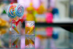 Colorful lolipop and mini cone in plastic box with reflection. On mirror Stock Photo