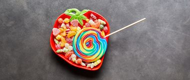 Colorful lollipop and candy sweets. In strawberry shaped bowl on studio background Royalty Free Stock Images