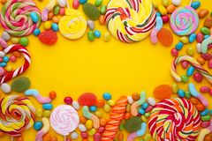Colorful lollipops and different colored round candy on yellow background royalty free stock photography