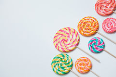 Colorful lollipops on sticks on white table. Sweet caramel candy. Colorful lollipops on sticks organised on white table. Sweet caramel candy pattern. Celebration Royalty Free Stock Photography