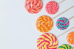Colorful lollipops on sticks on white table. Sweet caramel candy. Colorful lollipops on sticks organised on white table. Sweet caramel candy pattern. Celebration Royalty Free Stock Image