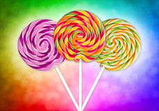 Colorful lolly pops. Three lolly pops in front of colorful background Royalty Free Stock Photography