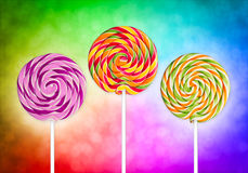 Colorful lolly pops. Three lolly pops in front of colorful background Royalty Free Stock Images