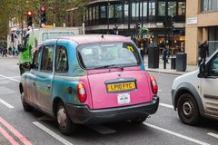 Colorful London taxi cab is on the street Stock Photos