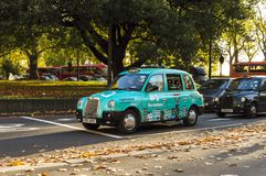 Colorful London taxi on the street. Sunny day in London Stock Photo