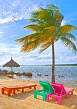 Colorful lounge chairs at a tropical paradise beach. In Florida Keys. Beautiful aqua green waters of the ocean, hanging palm trees and a blue sky in the Royalty Free Stock Photos