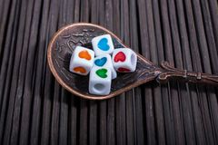 Colorful love cubes in a spoon. On a straw mat Stock Images