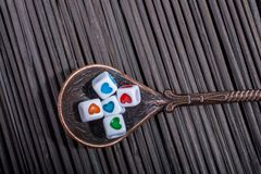 Colorful love cubes in a spoon. On a straw mat Stock Photo