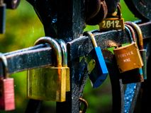Colorful love locks hanged on bridge. stock images