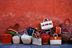 Colorful luggage and bags by a red wall. Royalty Free Stock Photos