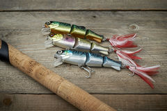 Colorful lures with the fishing rod on the wooden pier Stock Photos