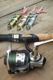 Colorful lures with the fishing rod on the wooden pier Stock Image