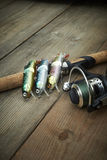 Colorful lures with the fishing rod on the wooden pier Royalty Free Stock Image