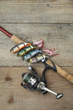Colorful lures with the fishing rod on the wooden pier Royalty Free Stock Images