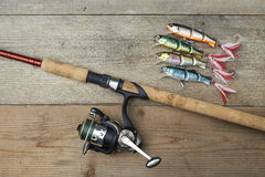 Colorful lures with the fishing rod on the wooden pier. Lot of colorful lures with the fishing rod on the wooden pier Stock Photos