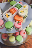 Colorful macaron cookies on bar for sale. Beautiful Macarons choice. Plenty of colorful french cookies, meringue based confectionery desserts on counter bar for Stock Image