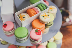Colorful macaron cookies on bar for sale. Beautiful Macarons choice. Plenty of colorful french cookies, meringue based confectionery desserts on counter bar for Stock Images