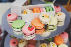 Colorful macaron cookies on bar for sale. Beautiful Macarons choice. Plenty of colorful french cookies, meringue based confectionery desserts on counter bar for Stock Photography