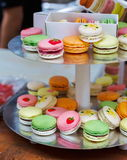 Colorful macaron cookies on bar for sale. Beautiful Macarons choice. Plenty of colorful french cookies, meringue based confectionery desserts on serving plate at Royalty Free Stock Image