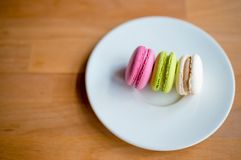 Colorful macaron or macaroon on plate royalty free stock photo
