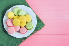 Colorful macaron in a plate on wooden, pink background. Selective focus, top view, macro, toned image, film effect Royalty Free Stock Images