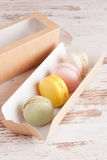 Colorful macarons in the box on white background. Colorful macarons on white background, close up, vertical Stock Image
