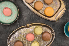 Colorful macarons in colored metal bowls Royalty Free Stock Photos