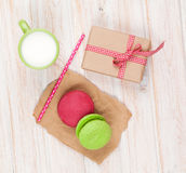 Colorful macarons, cup of milk and gift box Stock Photos