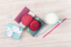 Colorful macarons, cup of milk and gift box Stock Images