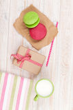 Colorful macarons, cup of milk and gift box Royalty Free Stock Photo