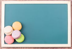 Macarons on a chalkboard top view. Colorful macarons on a green chalkboard close up Stock Photos