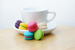 Colorful macarons and milk cup. On wooden background Royalty Free Stock Photo