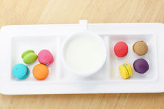 Colorful macarons and milk cup. On wooden background Stock Photography