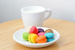 Colorful macarons and milk cup. On wooden background Stock Images