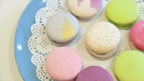 Traditional brightly painted French pasta on a blue plate. Colorful macarons on a plate close-up macro stock video