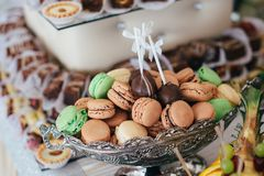 Colorful macarons on pyramid-shaped plastic tower stand as part of candy bar sweet table Stock Photo