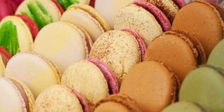 Colorful macarons in the shop window. Tasty colorful appetizing lie on the shop window or in a cafe stock images