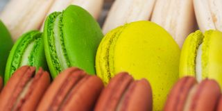 Colorful macarons in the shop window. Tasty colorful appetizing lie on the shop window or in a cafe stock photography