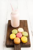 Colorful macaroons and bottle of milk on vintage cutting board Royalty Free Stock Photography