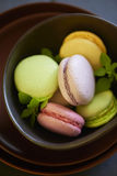 Colorful macaroons on brown plate Royalty Free Stock Photos