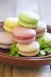 Colorful macaroons on brown plate Stock Images